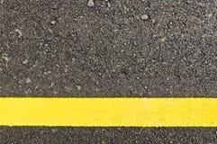 Primo piano alla strada asfaltata con la linea gialla Fotografia Stock
