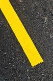 Primo piano alla strada asfaltata con la linea gialla per fondo Fotografia Stock