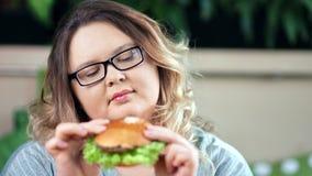Primo piano appetitoso fresco considerante dubbioso stante a dieta messo a fuoco premuroso dell'hamburger della donna grassa archivi video
