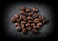 Primo piano arrostito dei chicchi di caffè su fondo nero fotografie stock libere da diritti