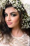Primo piano attraente caucasico della donna con i gigli sulla testa su bianco Immagini Stock Libere da Diritti