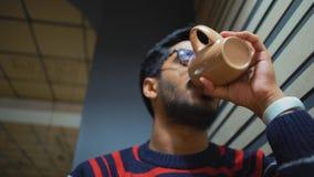Primo piano, caffè bevente del tipo indiano inferiore di vista e guardare uno smartphone archivi video