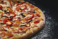 Primo piano caldo fresco della pizza deliziosa sulla tavola nera con sparso immagine stock