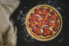 Primo piano caldo fresco della pizza deliziosa sulla tavola nera con sparso immagini stock