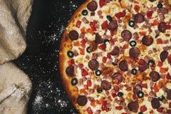 Primo piano caldo fresco della pizza deliziosa sulla tavola nera con sparso immagine stock libera da diritti