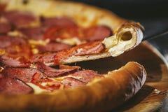 Primo piano caldo fresco della pizza deliziosa sulla tavola nera con sparso fotografia stock libera da diritti
