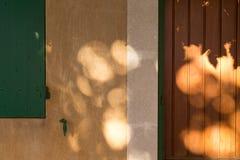 Primo piano caldo giallo della facciata con gli otturatori verdi e la porta di legno Fotografie Stock Libere da Diritti