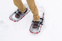 Primo piano, camminante nella neve in dispositivi speciali, racchette da neve, per migliore manovrabilità fotografia stock libera da diritti