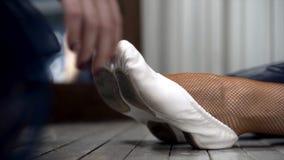 Primo piano che allunga le ballerine sul pavimento azione Primo piano di allungamento della ballerina dei calzini in scarpe del p immagine stock