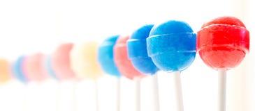 Primo piano colorato delle lecca-lecca e sbiadirsi in un fondo bianco Fotografie Stock Libere da Diritti