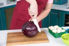 Primo piano come cuoco che taglia cavolo rosso con il coltello bianco La mano bella del ` s dell'uomo ha tagliato il cavolo rosso Immagine Stock Libera da Diritti
