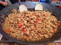 Primo piano con la cottura della carne su un wok caldo con le certi erbe ed ingrediente tradizionali immagini stock