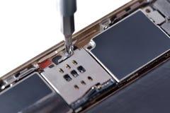 Primo piano con la riparazione usata dello smartphone con il cacciavite Immagine Stock