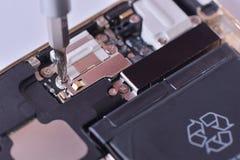Primo piano con la riparazione usata dello smartphone con il cacciavite Immagine Stock Libera da Diritti