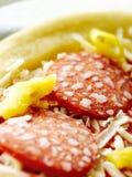 Primo piano congelato della pizza di merguez e del salame Immagine Stock