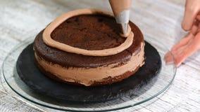 Primo piano: crema del biscotto sotto forma di spirale sul dolce Pan di Spagna del cioccolato con crema Preparazione del dolce in video d archivio