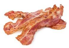 Primo piano cucinato delle fette di lardo del bacon isolato su un fondo bianco fotografia stock libera da diritti