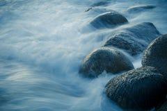 Primo piano dalle onde che gonfiano sopra le rocce sulla riva Esposizione lunga Fotografie Stock Libere da Diritti
