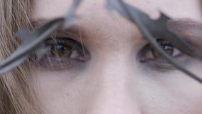 Primo piano degli occhi di una giovane donna attraverso filo spinato azione Concetto di modo di bellezza archivi video