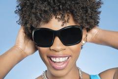 Primo piano degli occhiali da sole d'uso della giovane donna allegra con le mani dietro la testa sopra fondo colorato fotografia stock