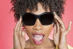 Primo piano degli occhiali da sole d'uso di una donna afroamericana sopra fondo colorato fotografie stock