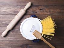 Primo piano degli spaghetti dentro un vaso accanto ad una forcella di legno e un rullo sulla tavola di legno Immagine Stock Libera da Diritti