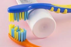 Primo piano degli spazzolini da denti e del dentifricio in pasta del bambino sul fondo di colore Immagini Stock