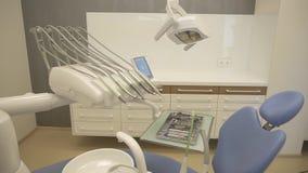 Primo piano degli strumenti in gabinetto del dentista Strumenti dell'acciaio inossidabile in vassoio del metallo, macchina della  video d archivio