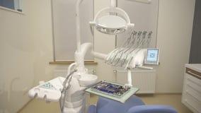 Primo piano degli strumenti sulla sedia del dentista Strumenti dell'acciaio inossidabile in vassoio del metallo, macchina della s video d archivio