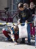 Primo piano dei bambini che raccolgono caramella dall'asfalto Fotografia Stock Libera da Diritti