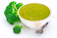 Primo piano dei broccoli deliziosi crema in una ciotola foreground Include i broccoli freschi fotografia stock libera da diritti