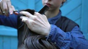 Primo piano dei capelli di taglio del parrucchiere della giovane donna dell'uomo di mezza età sconosciuto dei pantaloni a vita ba video d archivio