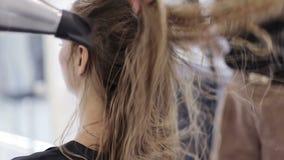 Primo piano dei capelli femminili lunghi maschii dell'apparecchio per asciugare le mani facendo uso dell'essiccatore elettrico stock footage