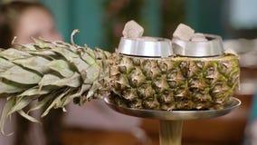 Primo piano dei carboni caldi su una ciotola di narghilé dell'ananas stock footage