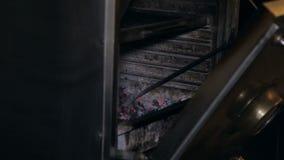 Primo piano dei carboni mescolantesi di un uomo in una stufa professionale del barbecue in ristorante archivi video