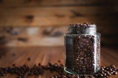 Primo piano dei chicchi di caffè in un barattolo di vetro su fondo di legno immagine stock