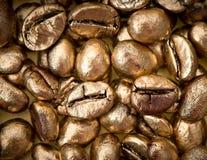 Primo piano dei chicchi di caffè dorati Fotografia Stock