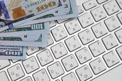 Primo piano dei contanti del dollaro sulla tastiera di computer immagini stock libere da diritti