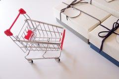 Primo piano dei contenitori e del carrello di regalo sullo scrittorio bianco fotografie stock