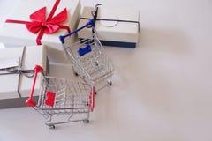 Primo piano dei contenitori e del carrello di regalo sullo scrittorio bianco fotografia stock
