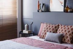 Primo piano dei cuscini modellati che si trovano su un letto molle in camera da letto int Immagine Stock Libera da Diritti