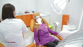 Primo piano dei denti d'esame del ` s della giovane donna del dentista stock footage