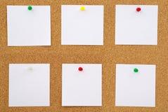 Primo piano dei documenti di nota sulla scheda del sughero Immagine Stock