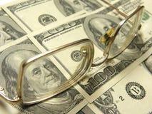 Primo piano dei dollari e degli occhiali Fotografie Stock Libere da Diritti