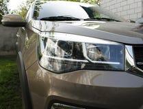 Primo piano dei fari automobilistici moderni del LED all'aperto su un'automobile marrone da un produttore cinese immagini stock libere da diritti