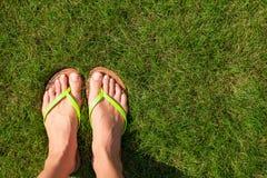 Primo piano dei Flip-flop e delle gambe luminosi su verde Fotografia Stock