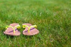 Primo piano dei Flip-flop luminosi su erba verde Fotografie Stock Libere da Diritti
