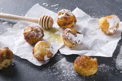Primo piano dei fori fritti nel grasso bollente deliziosi della ciambella con formaggio, miele e zucchero in polvere dolce sui pr immagini stock libere da diritti