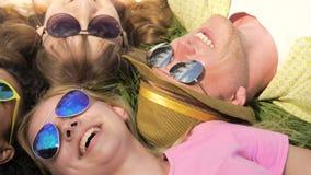 Primo piano dei fronti degli amici, delle ragazze felici e dei tipi trovantesi sull'erba, scherzando, ridente archivi video