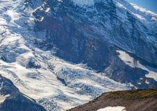 Primo piano dei ghiacciai del monte Rainier con due genti minuscole Fotografie Stock